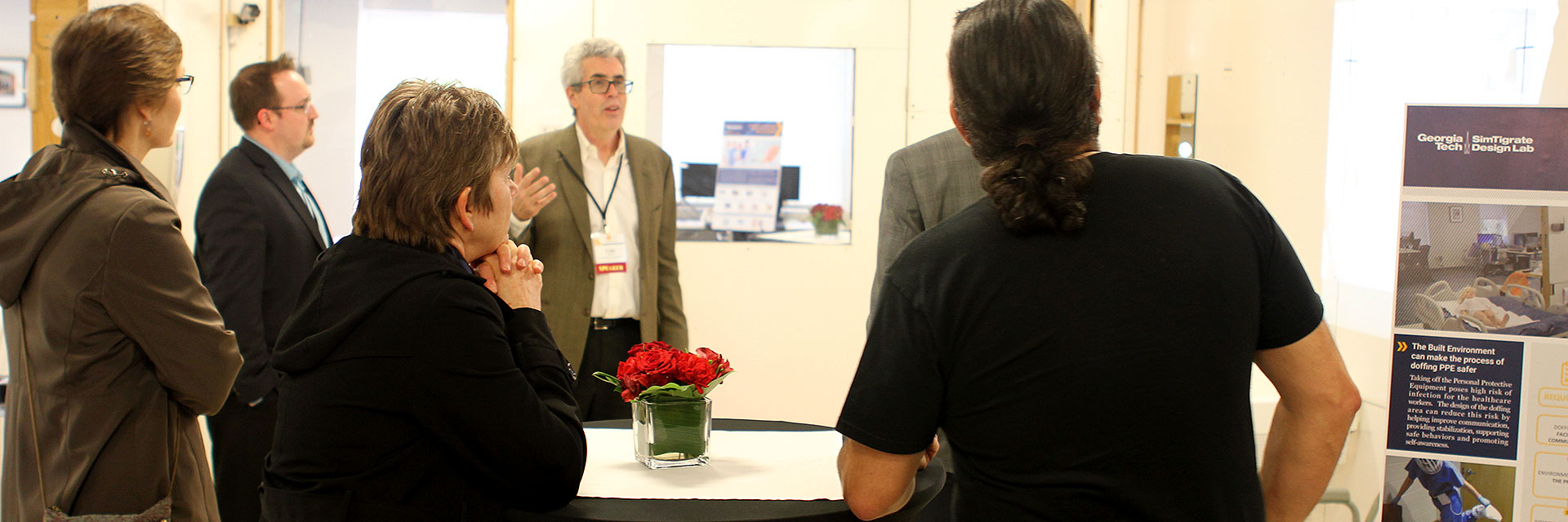 Craig Zimring talks with visitors at an event at SimTigrate.