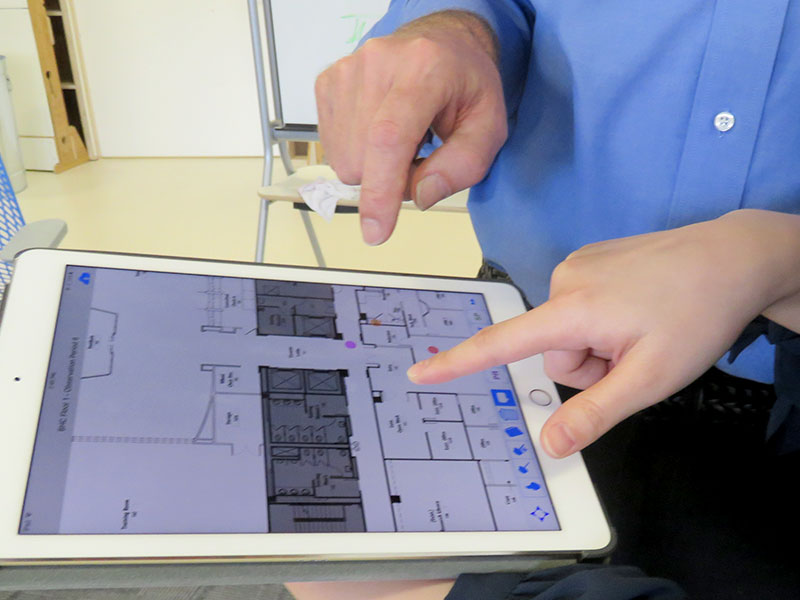 Researchers look at a floorplan on a laptop.