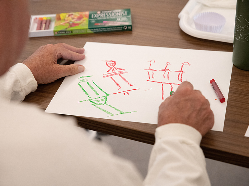 A man draws images in crayon as part of the program.